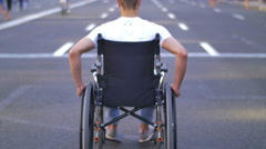 Invalid man sit and ride in the wheel chair in the crowd stream at sidewalk - stock footage
