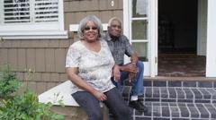 Happy senior black couple sitting smiling at camera Stock Footage