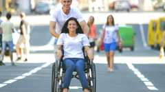 The man carry invalid woman in the wheelchair in the crowd stream - stock footage