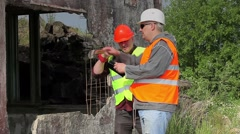 Construction employee with cell phone near damaged building Stock Footage