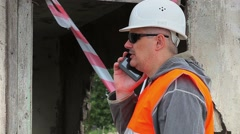 Construction employees with cell phone near unfinished building Stock Footage