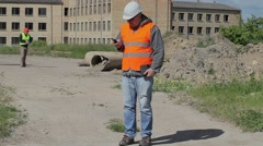 Construction employees with cell phone and documents Stock Footage