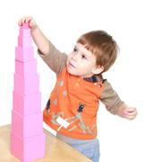 Little boy learn to put pink pyramid in Montessori kindergarten - stock photo