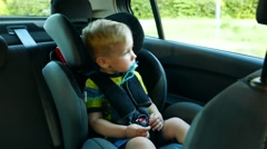 Kid baby child boy toddler in the children's car seat in the car rides Stock Footage