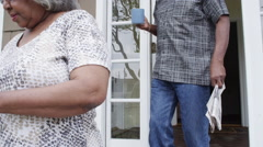 African senior couple shooing away unwanted visitors - stock footage