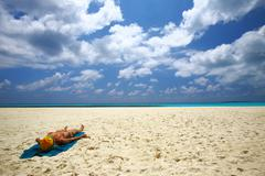 Young women is sunburning on the coral sandy beach - stock photo