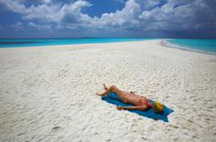 Young women is sunburning on the infinity coral sandy beach Stock Photos