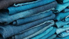 Neat Stacks of Folded Denim Trousers Stock Footage