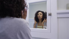 Black woman fixing hair in the bathroom Stock Footage