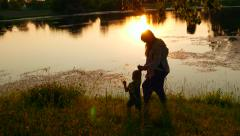 Happy family, loving mother with a baby kid child walks near a lake at sunset Stock Footage