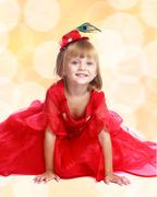 Fashionable blonde girl in a bright red dress sitting on the flo - stock photo