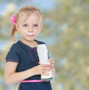Girl smeared lips milk which she drinks out of a big hand , clos Stock Photos