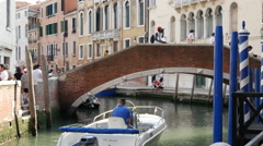 Boat passing by a bridge in Rio Nuovo Canal in Venice Italy - stock footage