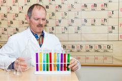 Chemistry teacher filling colored test tubes Stock Photos