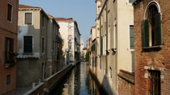 Narrow canal with houses in Venice Italy Stock Footage