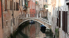 Narrow canal with a bridge and houses in Venice Italy Stock Footage