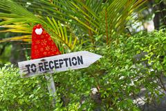 Funny wooden pointer to reception of a tropical hotel with christmas hat, Mal - stock photo