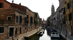 Narrow canal with houses and boats in Venice Italy Stock Footage