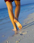Women's legs on a sandy beach - stock photo