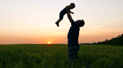 Happy family, loving father picks up in hands and amuse kid baby child at sunset Stock Footage
