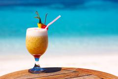 Bocal of fruity cocktail on a beach table - stock photo