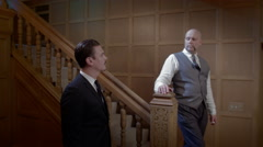 Stock Video Footage of 1950s retro-styled men with cigarettes in wood paneled hall 4K