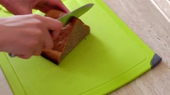 Woman cutting bread with a knife Stock Footage