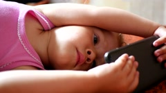 Little girl watching cartoons on a screen of mobile phone lying on a sofa - stock footage