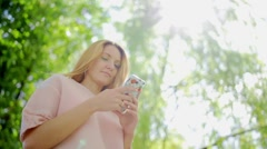 Happy girl typing on phone and smiling Stock Footage