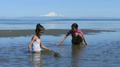 Two Cute Asian Sisters Playing In The Sand At Low Tide Stock Footage