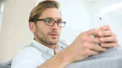 Portrait of man with eyeglasses sending message with smartphone Stock Footage