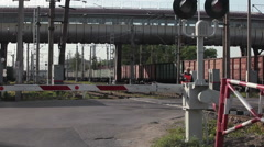 Freight train passes railway crossing with closed barriers, Russia Stock Footage
