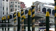 Pier with yellow green poles with Ponte di Rialto at the background Stock Footage