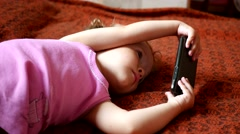 Little girl watching cartoons on a screen of mobile phone lying on a sofa Stock Footage