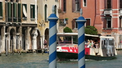 Blue poles with ferry passing by in the background in Venice, Italy Stock Footage