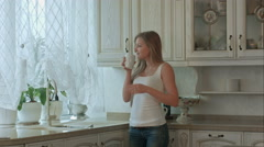 Beautiful girl drinks tea on kitchen at morning Stock Footage