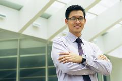 Portrait Chinese Businessman Smiling Outside Office Text Space - stock photo