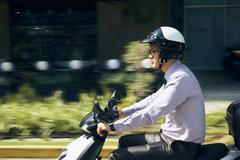 Chinese Businessman Commuter Riding Scooter Motorcycle In City Stock Photos