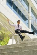 Happy Chinese Businessman Going Downstairs Sliding On Rail - stock photo