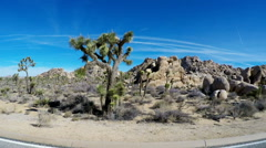 Vehicle Side View Passing Rock Mounds- Joshua Tree National Park Stock Footage