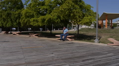 OLD MAN SPEAKING ON CELLPHONE on park bench - Condado Lagoon - Puerto Rico - stock footage