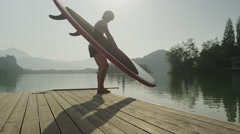 SLOW MOTION: Female placing SUP board into the lake water Stock Footage