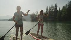 SLOW MOTION CLOSE UP: Girl friends oaring on stand up paddle boards - stock footage