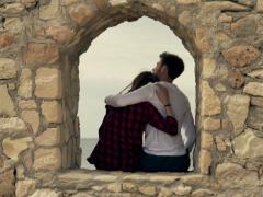 Young couple hugging while sitting on ancient ledge NTSC Stock Footage
