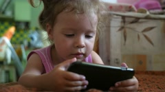 Little girl watching cartoons on a screen of mobile phone leaning on a bed Stock Footage