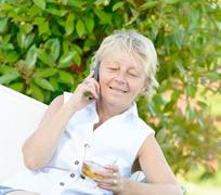 A woman sitting on phone with a drink Stock Photos