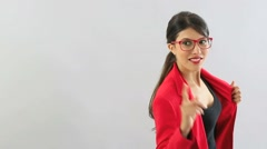 Woman with red jacket and eyeglasses pointing at camera Stock Footage
