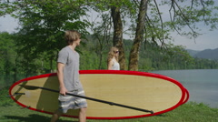 SLOW MOTION CLOSE UP: Young couple carrying stand up paddle boards towards water - stock footage