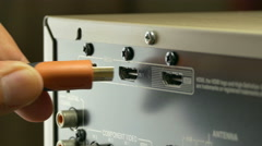 A close-up shot of a workman plugging-in an HDMI  - stock footage