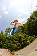 Young boy going airborne with a scooter Stock Photos